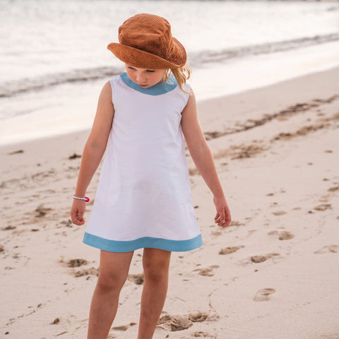 TukTuk Designs girls classic shift dress in cool white with blue trims and side pockets. Perfect for the beach, play dates and everyday.