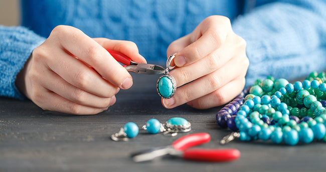 person using pliers to make jewelry