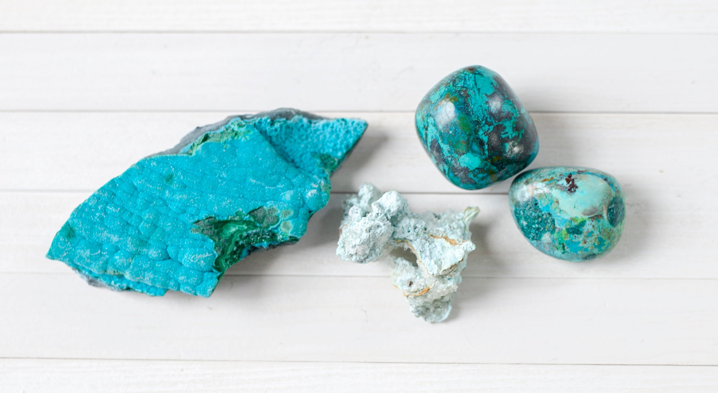 Raw and tumbled Chrysocolla. Chrysocolla is a unique mineral with vibrant teal color.