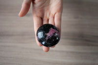 Rhodonite Stone | Large, Round Palm Stone Pebble | Black and Pink, 5oz