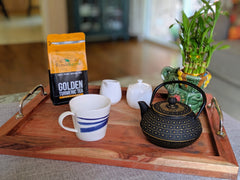 Golden turmeric healthy tea package shot along with tea set