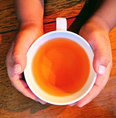hands holding a cup of black tea