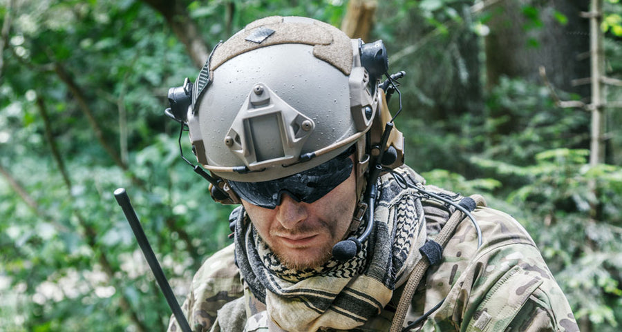 Soldier wearing ballistic helmet with OE coms
