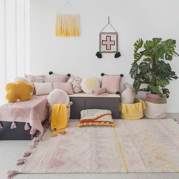 Interiors room setting with nude aztec rug and lots of nude, pink and ochre cushions and wall hangings