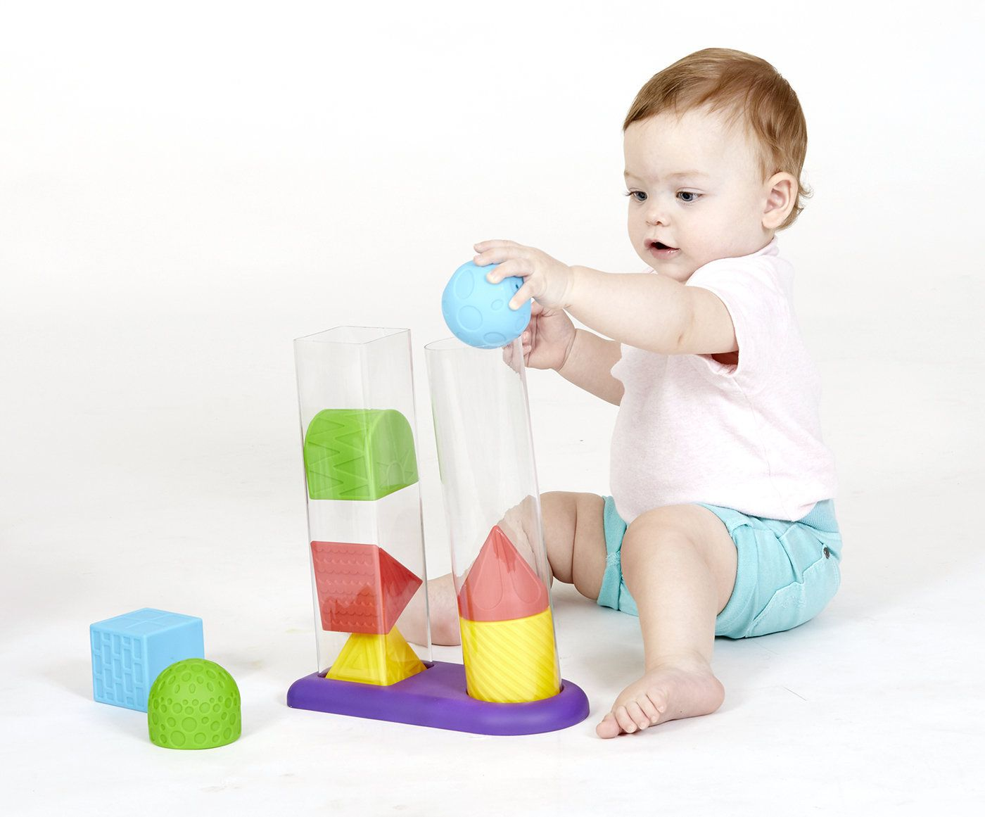 The Art of Christmas Shopping for… Other People's Kids. Child playing with Geostacker sensory toy.