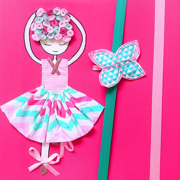 Designed to be hung on the wall, the picture of a tiny dancer is a combination of painted wood with layered fabric.