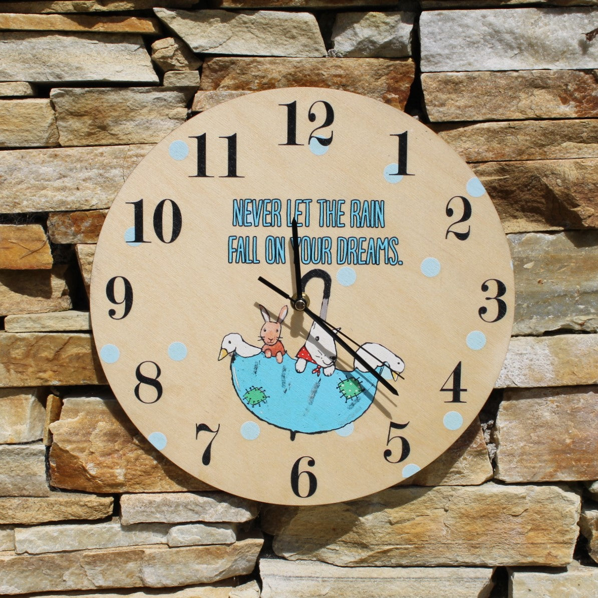 "Stained wooden clock with the motif ""Never let the rain fall on your dreams"" and a picture of animals in an umbrella."