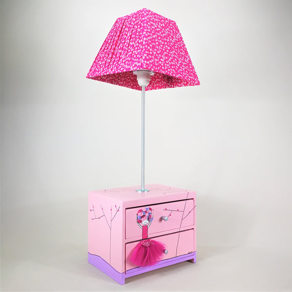 Designed and hand-crafted in Italy, this unique and stunning side lamp comes with two handy wooden drawers and is hand-painted throughout. The ballerina design is attained through cleverly layering fabrics.   The pretty pink drawer unit sits at the base of the lamp and is perfect for tidying away your child's small toys or accessories. The lampshade is handmade in deep pink fabric with white spots. T