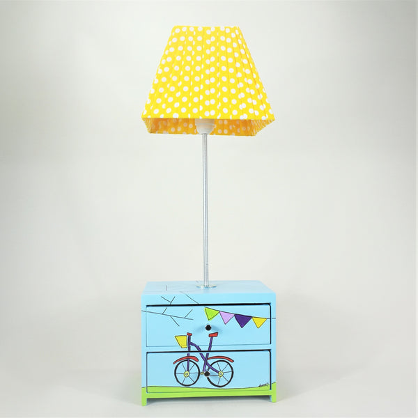 Designed and hand-crafted in Italy, this unique and stunning side lamp comes with two handy wooden drawers and is hand-painted throughout with a bicycle and bunting design.   The blue drawer unit sits at the base of the lamp and is perfect for tidying away your child's small toys or accessories. The lampshade is handmade in yellow fabric with white spots.
