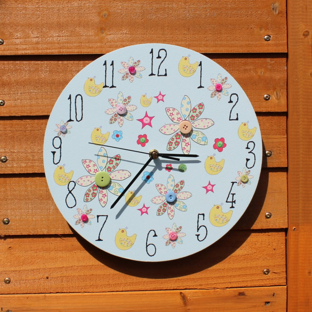 A pretty blue painted clock with pictures of flowers, birds and real buttons. Matching designs are available on other products on Rooms for Rascals.