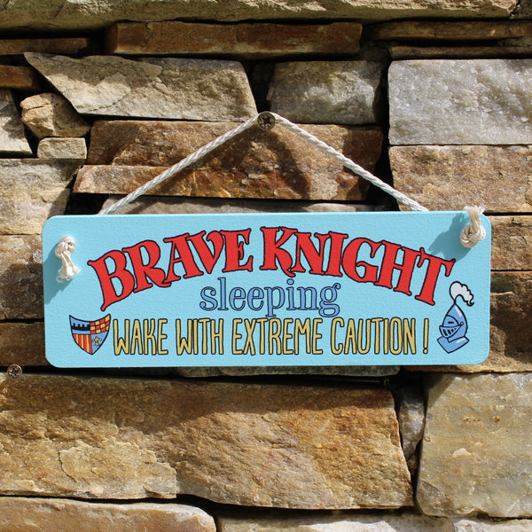 "Painted wooden board with motif ""Brave Knight sleeping - wake with extreme caution!"" comes with a string for hanging from the door."