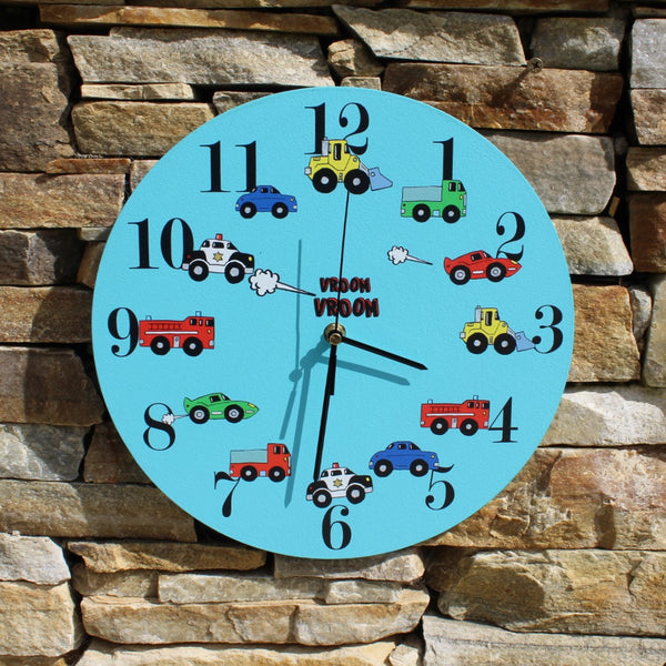 "A sleek blue painted clock with a different vehicle type beside each number and the motif ""vroom vroom"". Similar products are available on Rooms for Rascals."
