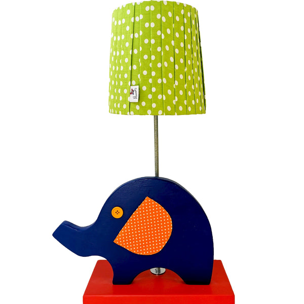 Designed and hand-crafted in Italy, this unique side lamp with a wooden base and an elephant design is perfect for your little explorer's bedroom.  Creatively constructed from wood and fabric, the dark blue elephant with orange ears and eyes on a red base is simply beautiful. The lime green lampshade with white spots is handmade and compliments the rest of the lamp.