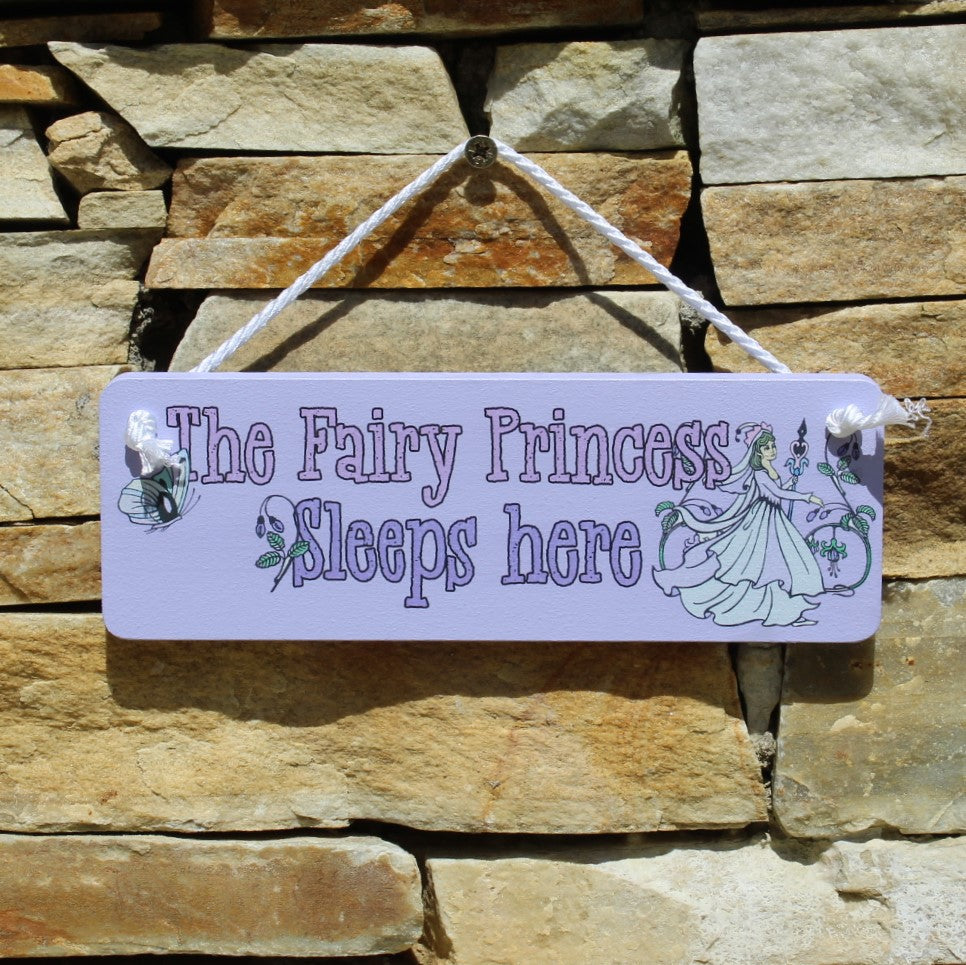 "Purple painted wooden board with motif ""The Fairy Princess Sleeps Here"" and a picture of a fairy princess, comes with a string for hanging from the door."