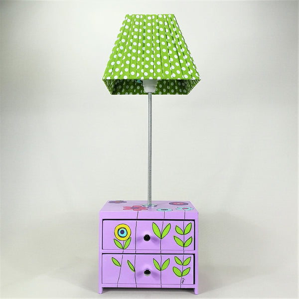 Designed and hand-crafted in Italy, this unique and stunning side lamp comes with two handy wooden drawers and is hand-painted throughout with a beautiful flower garden design.   The lilac drawer unit sits at the base of the lamp and is perfect for tidying away your child's small toys or accessories. The lampshade is handmade with a lime green fabric with white spots.