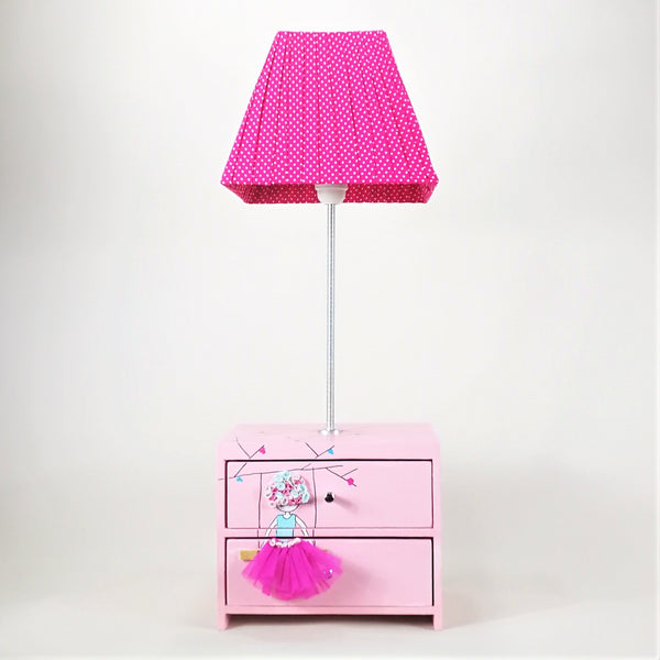 Designed and hand-crafted in Italy, this unique and stunning side lamp comes with two handy wooden drawers and is hand-painted throughout. The girl comes with a fuschia pink tulle dress and her hair is made by layering fabrics onto the wooden drawers.   The pretty pink drawer unit sits at the base of the lamp and is perfect for tidying away your child's small toys or accessories. The handmade lampshade is dark pink with small white spots.