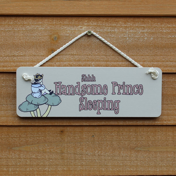"Painted wooden board with motif  ""Shhh Handsome Prince Sleeping"" and a picture of a prince sitting on a mushroom stool, comes with a string for hanging from the door."