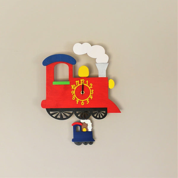 This red train clock springs to life with a moving blue mini-train as a pendulum. The clock face is on the train carriage.