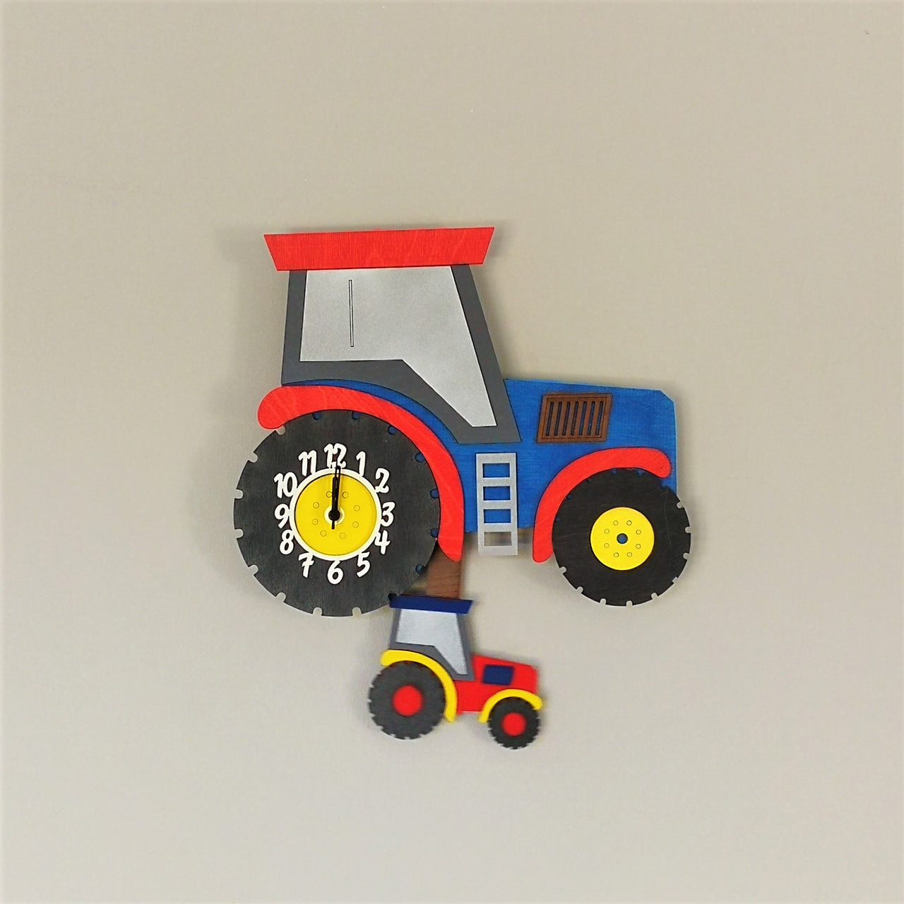 This blue tractor clock springs to life with a moving red mini-tractor as a pendulum. The clock face itself is on the big tractor wheel.