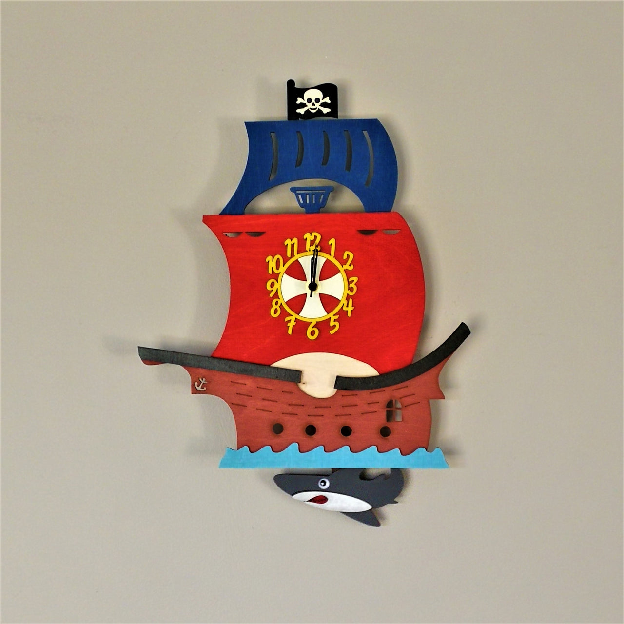 This colourful clock comes alive as a pirate ship sailing over shark-infested waters. The shark serves as a moving pendulum and the clock face is on the main sail of the pirate ship.