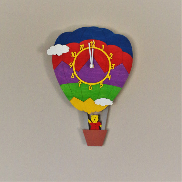 This colourful clock springs to life with a moving pendulum depicting a cute bear in a hot air balloon basket. The clock face is on the rainbow-coloured balloon.