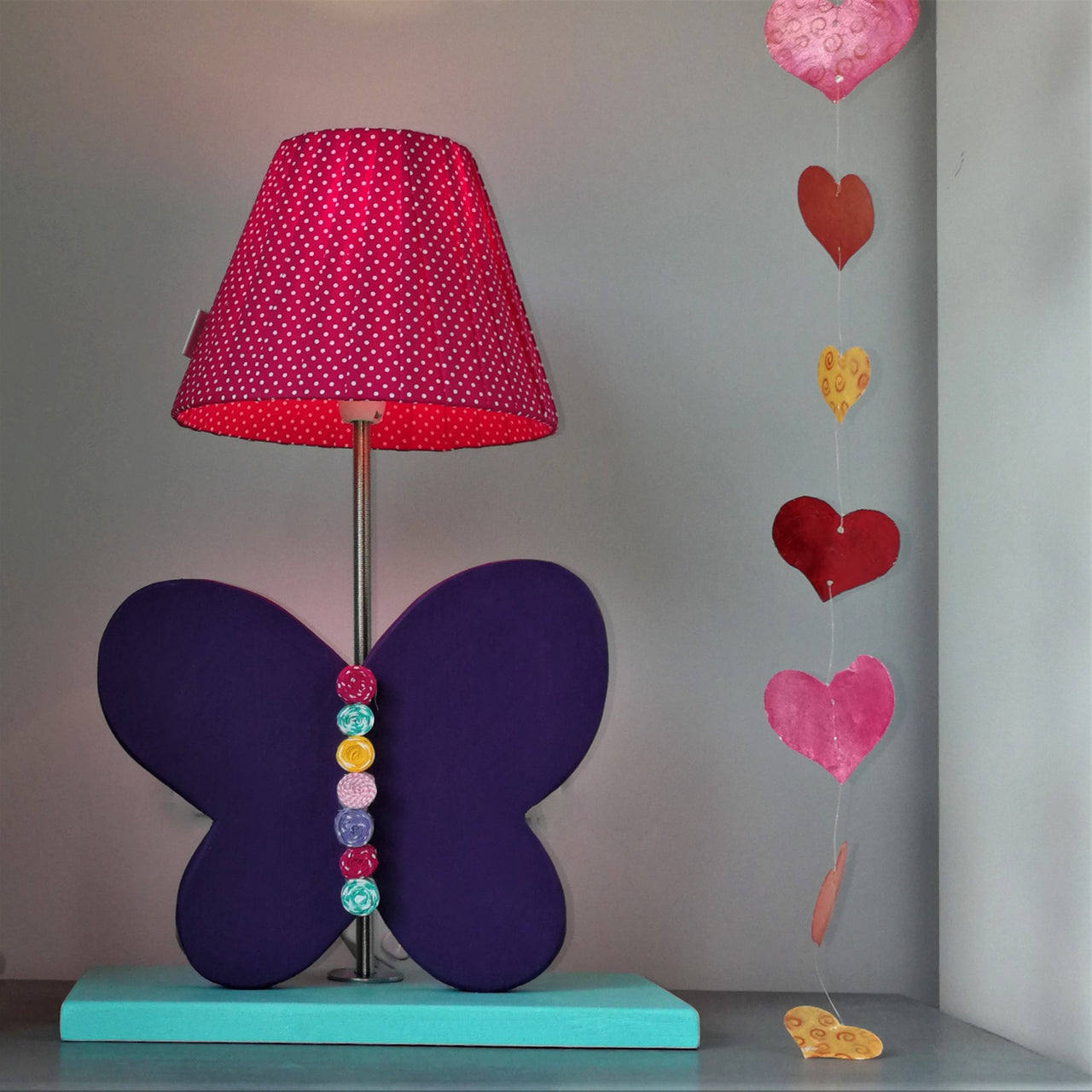 Stunning side lamp with a turquoise wooden base and a purple butterfly design. Creatively constructed from wood and layered fabric. The lampshade is handmade with matching deep pink fabric with white spots.