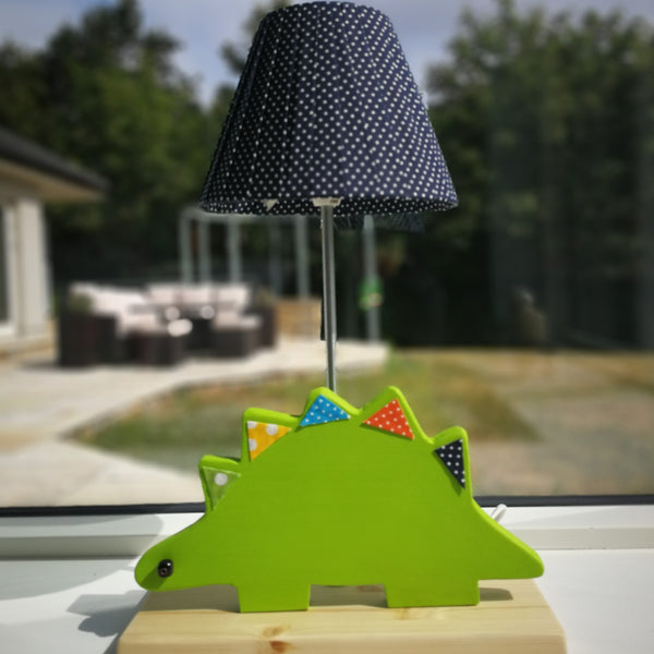 Close up of an exquisite side lamp with a wooden base and a green dinosaur design. Creatively constructed from wood and fabric.