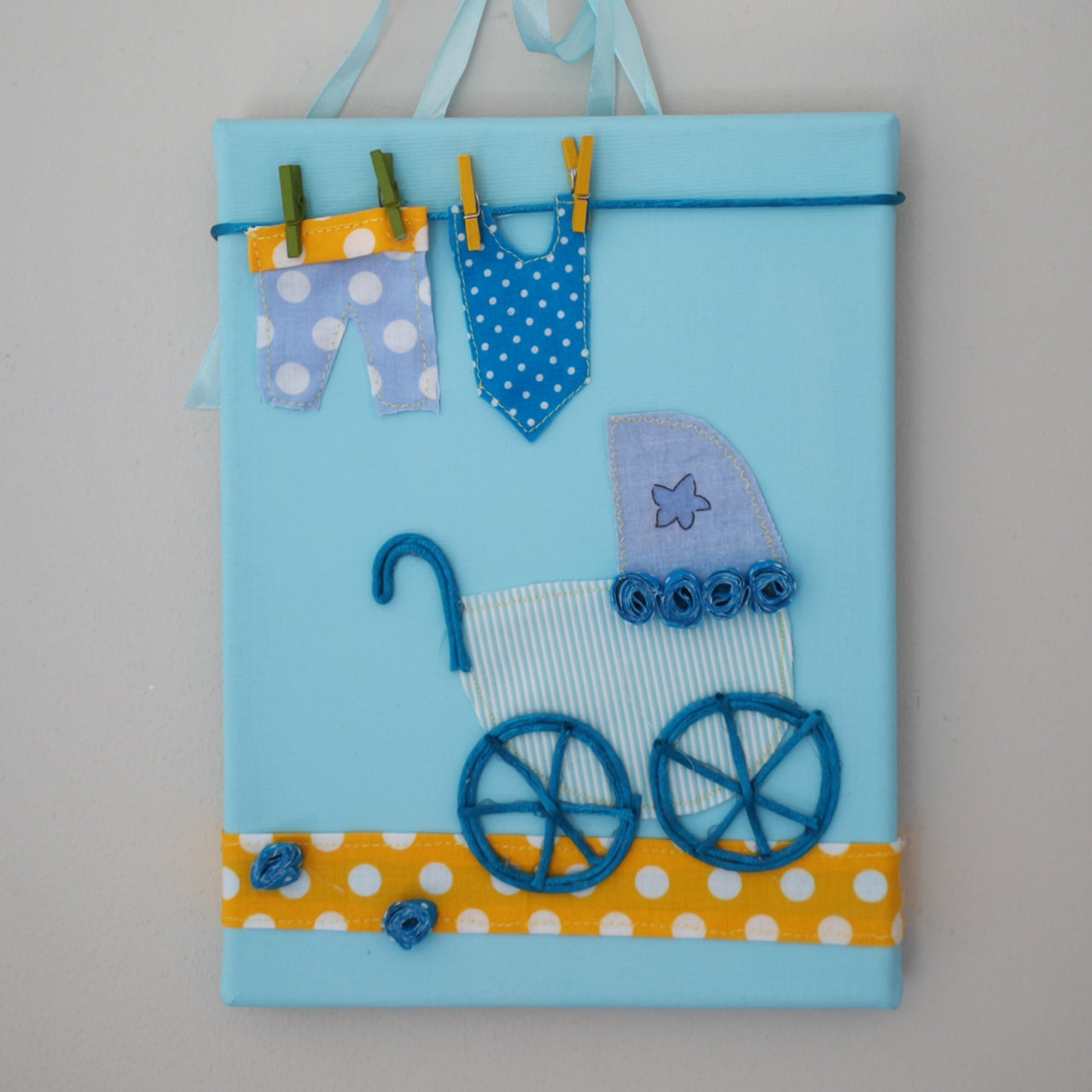 A beautiful Italian hand-crafted baby picture complete with an old style pram and washing line. It is the ultimate gift for a new baby or for their christening or baby-naming ceremony. Here in blue.