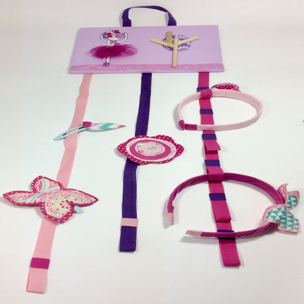 The ballerina headband and hairclip holder is designed to be hung on the wall. The ballerina picture is made of painted wood with layered fabric. Attached to the flower is three long ribbons for holding hairclips and notches for holding headbands.