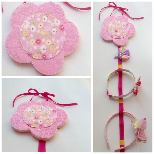 Three images of the flower headband and hairclip holder. Designed to be hung on the wall, the flower is made from painted wood with layered fabric. Attached to the flower is a long ribbon for holding hairclips and notches for holding headbands.