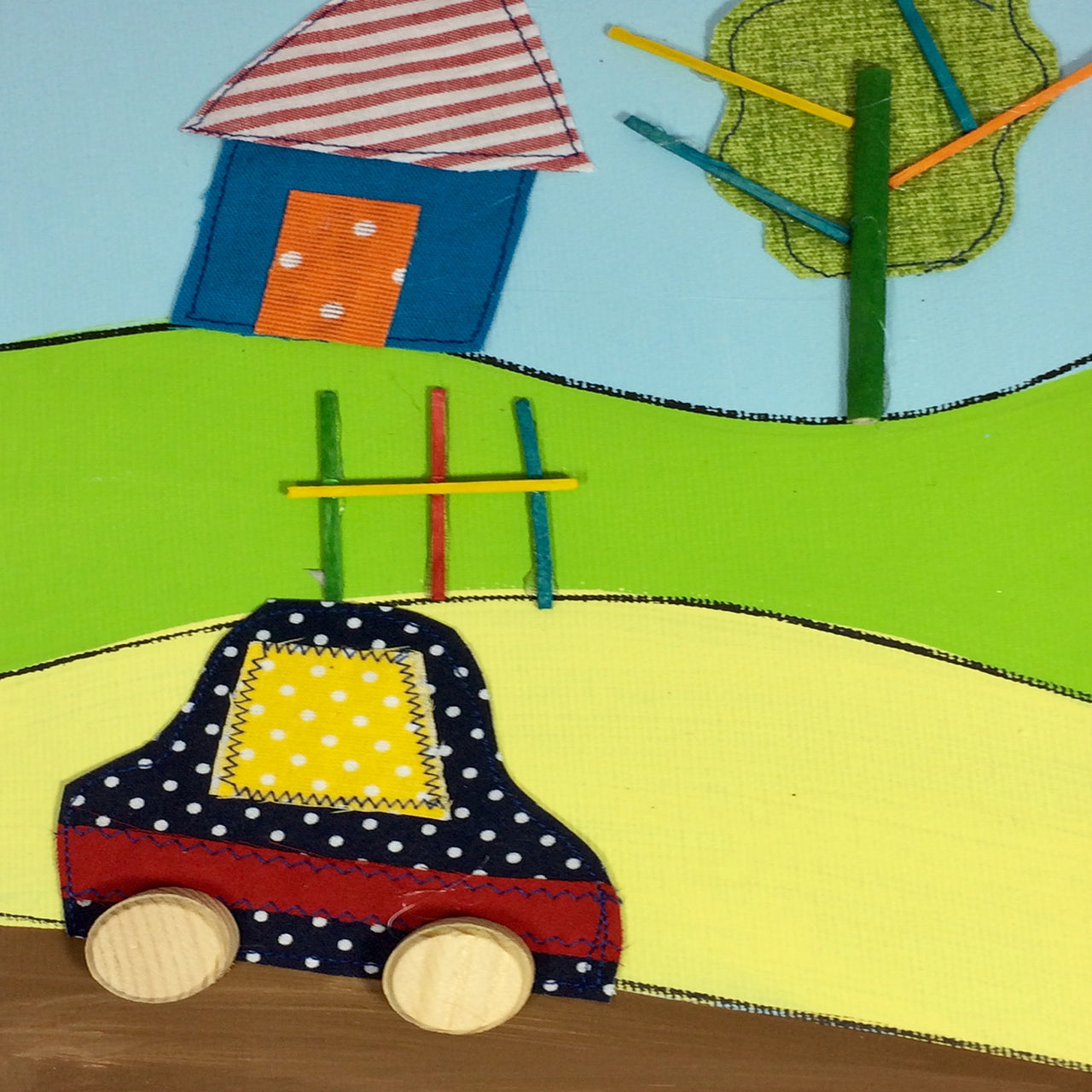 Picture of a car in the countryside on a painted canvas with layered fabrics to provide a three-dimensional effect.