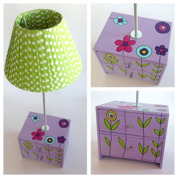 Three views of this unique and stunning side lamp with two wooden drawers. Hand-painted in throughout with a purple background and a flower garden design. Lime green lampshade with white spots.