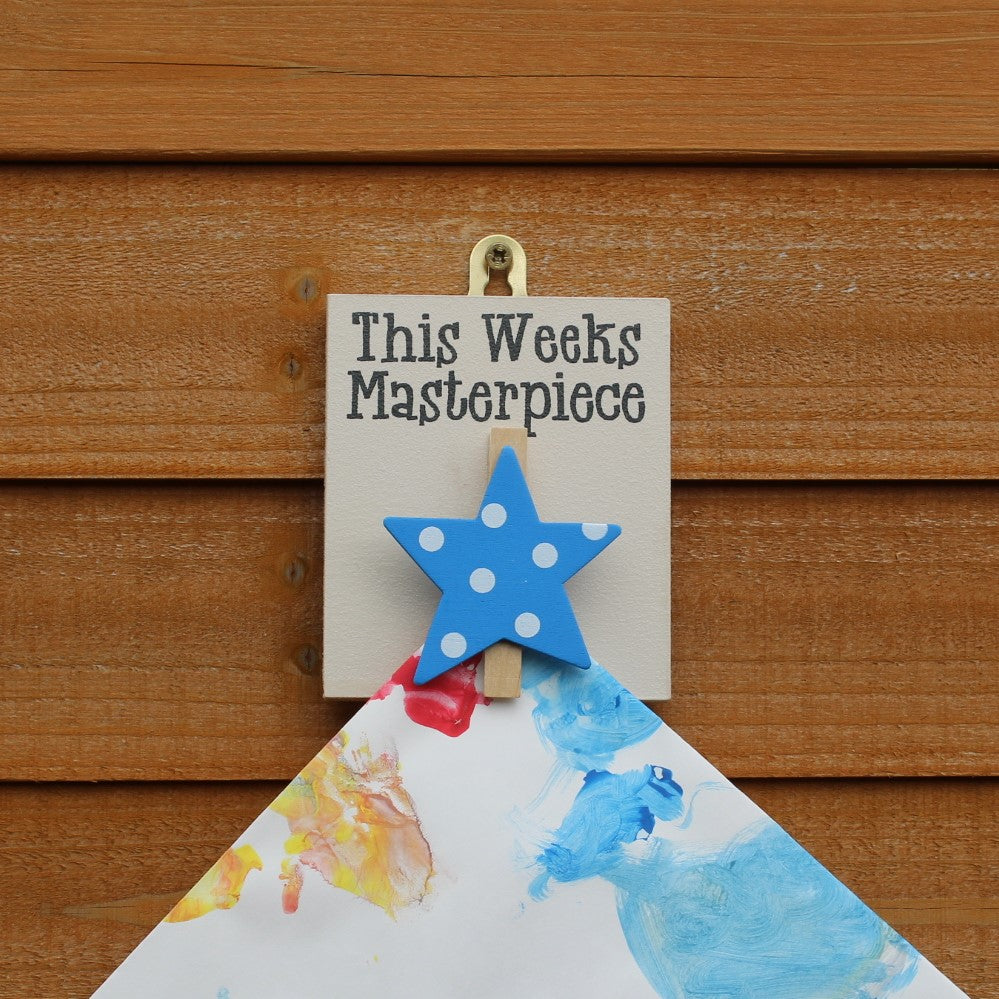 "Painted wooden board with a blue star peg and the motif ""This week's masterpiece"". Comes with a hook to hang from the wall."