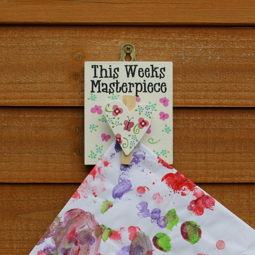 "White painted wooden base with heart-shaped peg in a flower and butterfly design. The message reads ""This Weeks Masterpiece"". Complete with a hook for hanging on the wall."