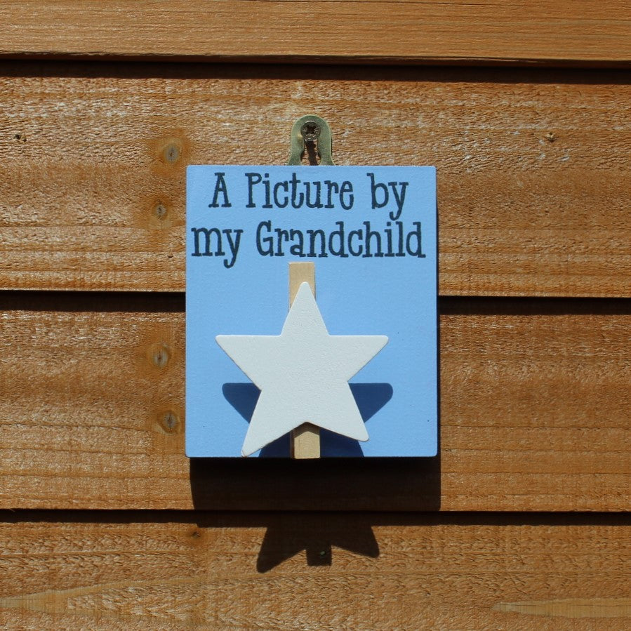 "Blue painted wooden base with star peg and the message ""A Picture by my Grandchild"". Complete with a hook for hanging on the wall."