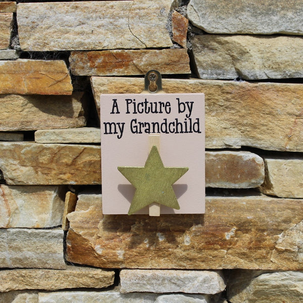 "Brown painted wooden base with gold star peg and the message ""A Picture by my Grandchild"", comes with a hook for hanging on the wall."