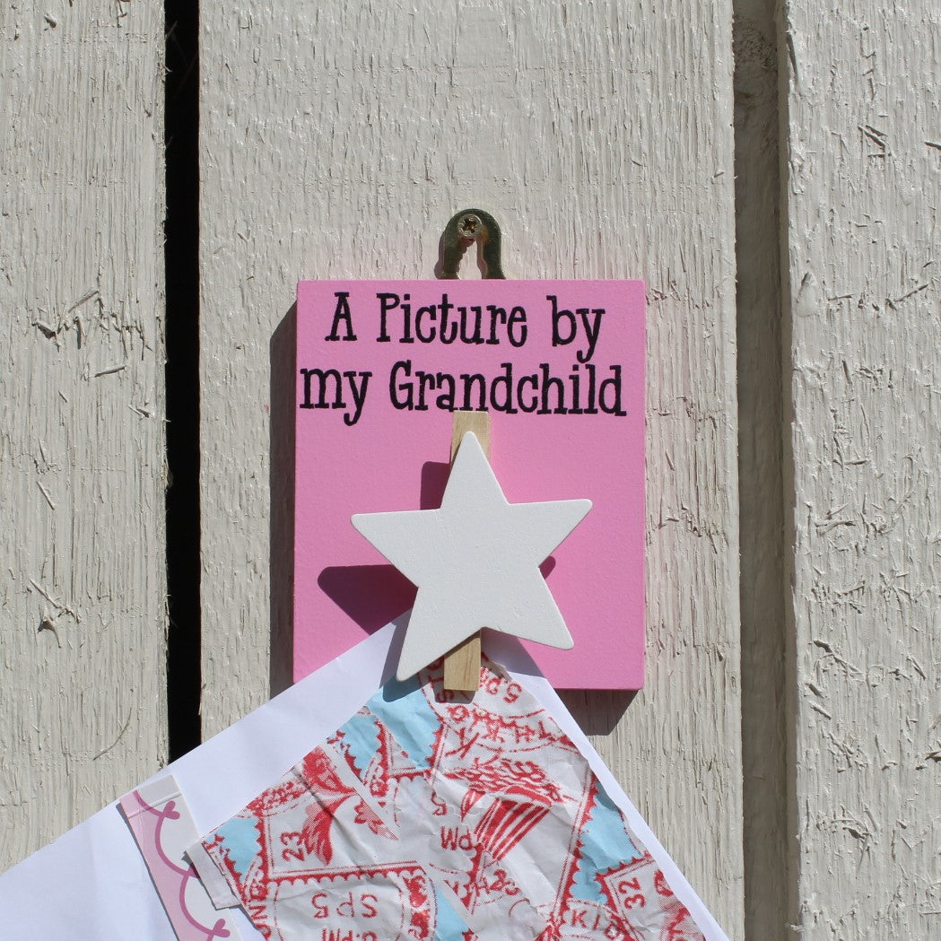"Pink painted wooden base with a white star peg and the message ""A Picture by my Grandchild"", comes with a hook for hanging on the wall."