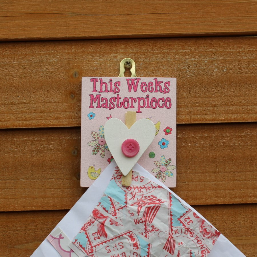 "Pink painted wooden base with a white heart peg and button flowers. The message reads ""This Weeks Masterpiece"". Complete with a hook for hanging on the wall."
