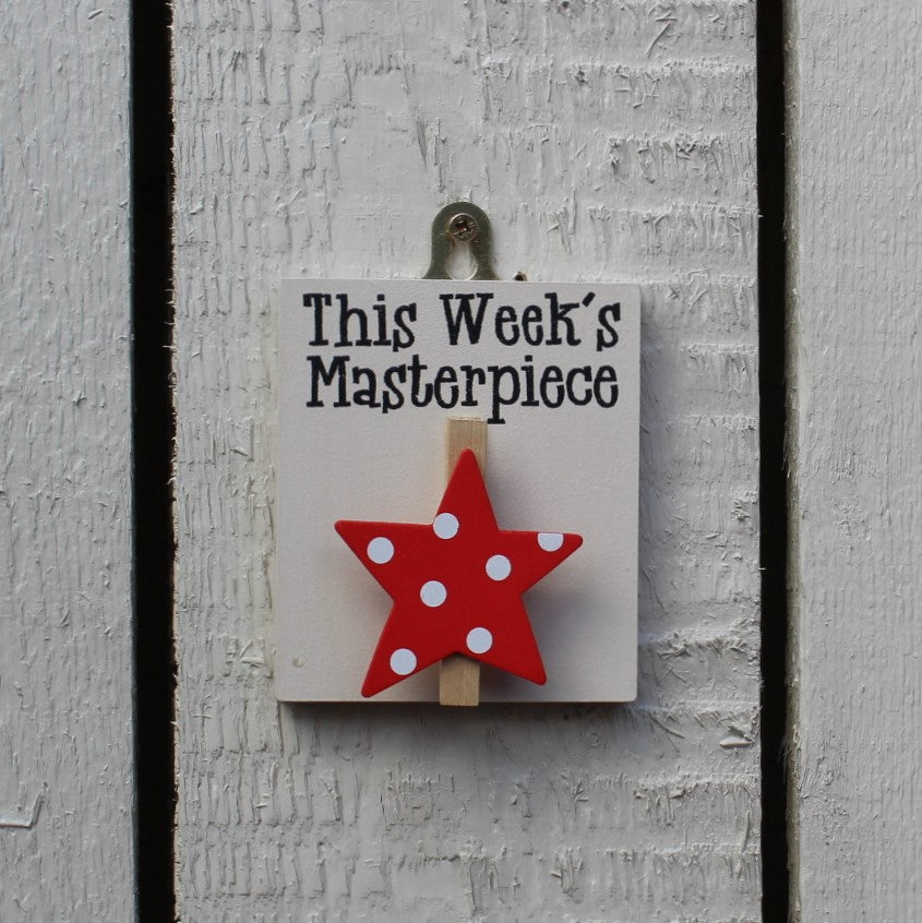 "Painted wooden base with a red star peg and the message ""This Week's Masterpiece"". Complete with a hook for hanging on the wall."