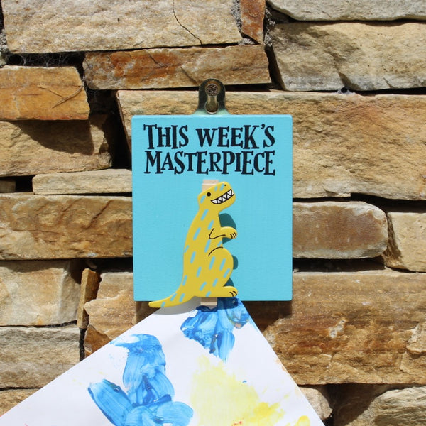 "Painted blue wooden base with yellow dinosaur peg and the message ""This Week's Masterpiece"". Complete with a hook for hanging on the wall."
