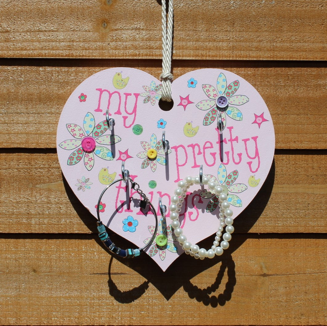 "Painted pink wooden heart with button flowers and six hangers with the message ""My pretty things"" and a string to hang it on the wall."