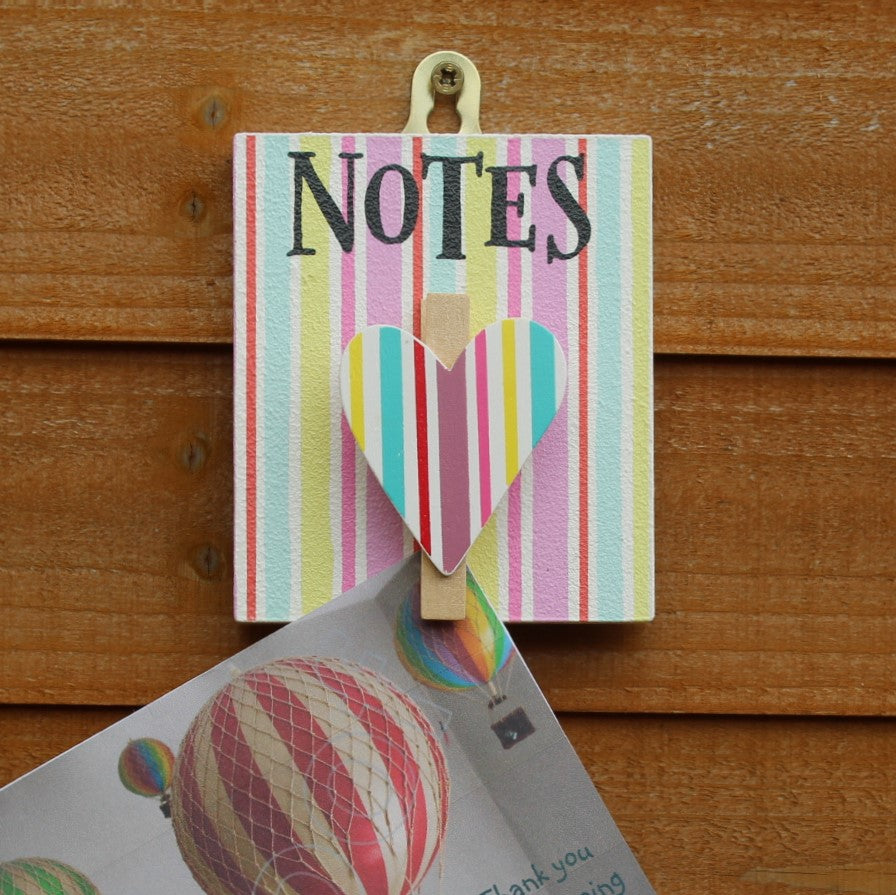 "Painted wooden board with colourful stripes and a heart shaped peg. It has the message ""Notes"" written on it and has a string for hanging from the wall."