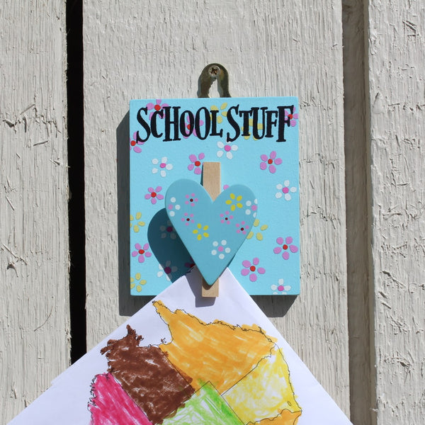 "Blue painted wooden board with colourful flowers and a heart shaped peg. It has the message ""School Stuff"" written on it and has a string for hanging from the wall."