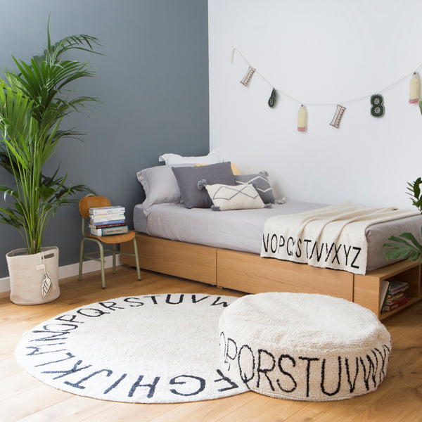 From A to Z… The versatile Round ABC collection pouffe from Lorena Canals made with a cotton exterior and is machine-washable. Image shows a bedroom with ABC rug and pouffe..