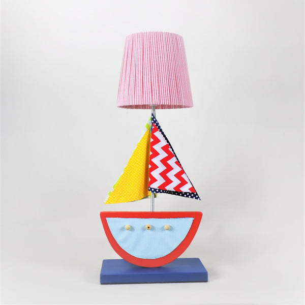 The most beautiful side lamp you will ever own! Designed and hand-crafted in Italy, this exquisite side lamp with a wooden base and a sea boat design will bring colour and imagination to your child's bedroom.   Creatively constructed from wood and layered fabric, the detail and finishing is amazing. The lampshade is handmade with matching red and white striped fabric.
