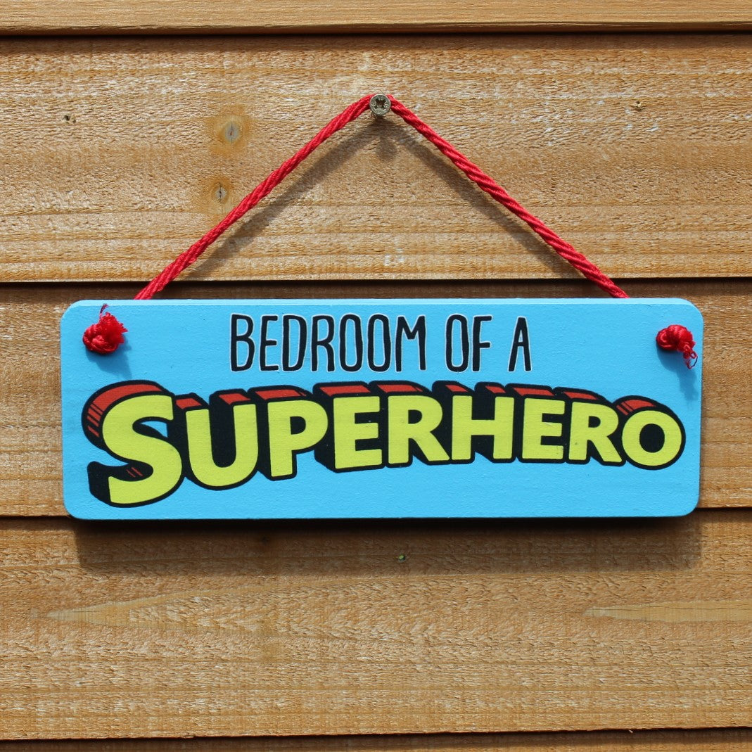 "Painted wooden board with motif ""Bedroom of a Superhero"" comes with a string for hanging from the door."