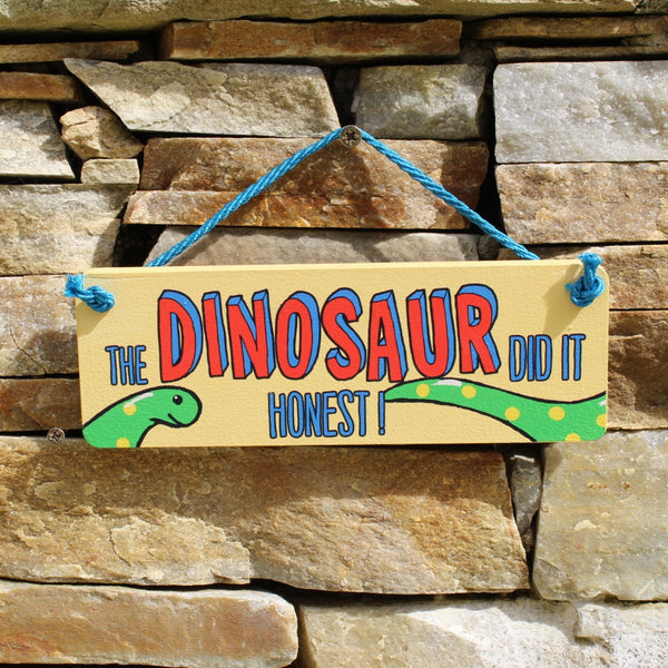 "Yellow wooden door hanger with the motif ""The Dinosaur did it, honest!"", with a string for hanging up."