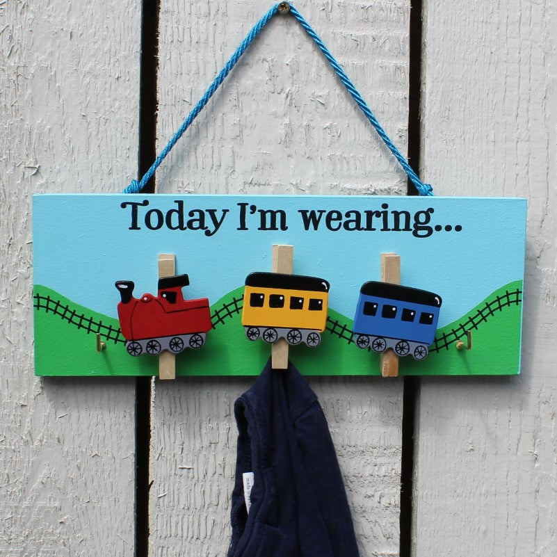 "Painted wooden board with three train pegs and two hooks for hanging clothes. Message reads ""Today I'm wearing"".  Complete with string for hanging on the wall."