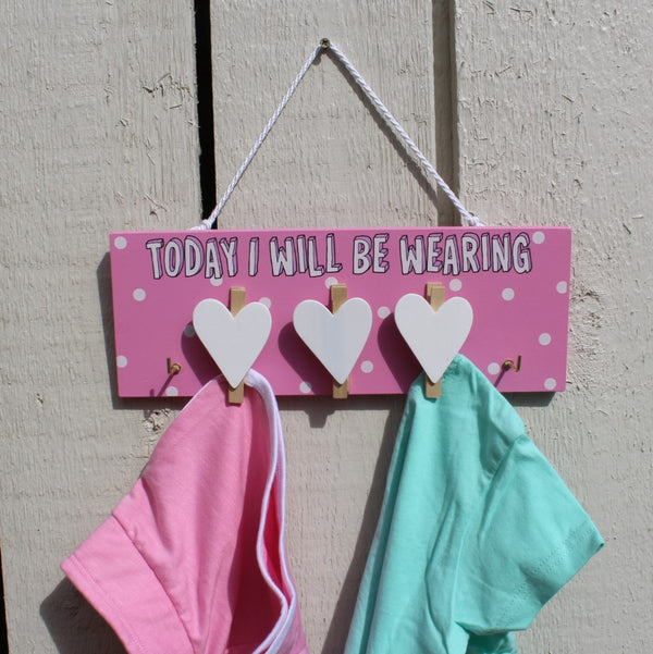 "Pink painted wooden board with three white heart pegs and two hooks for hanging clothes. Message reads ""Today I will be wearing"". Comes with a string for hanging from the wall."