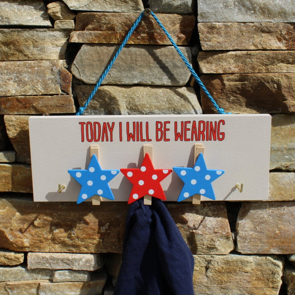 "Painted wooden board with three red and blue star pegs and two hooks for hanging clothes. Message reads ""Today I will be wearing"".  Complete with string for hanging on the wall."